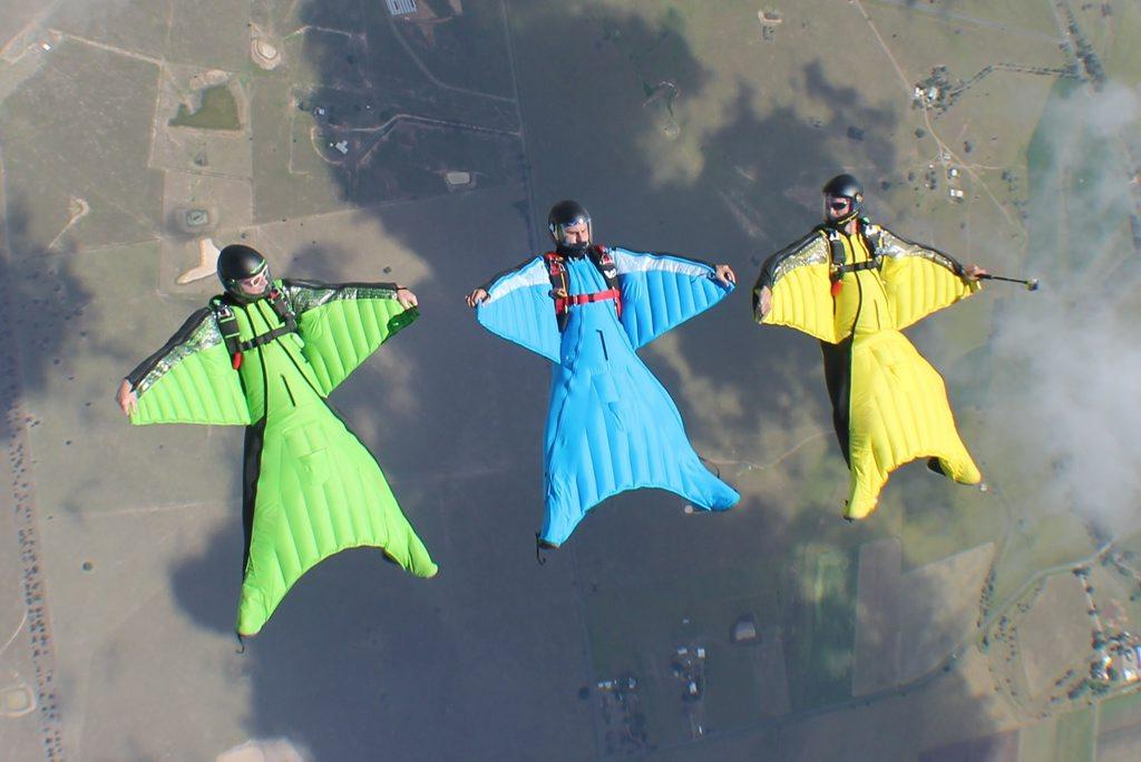 Sunshine Coast man Chris Byrnes (left) and his wingsuit pilot team mates Royce Wilson (centre) and Luke Rogers fly over Toogoolawah.