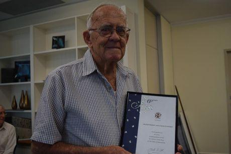 Graeme Pettigrew shows off his 60 years of service award.