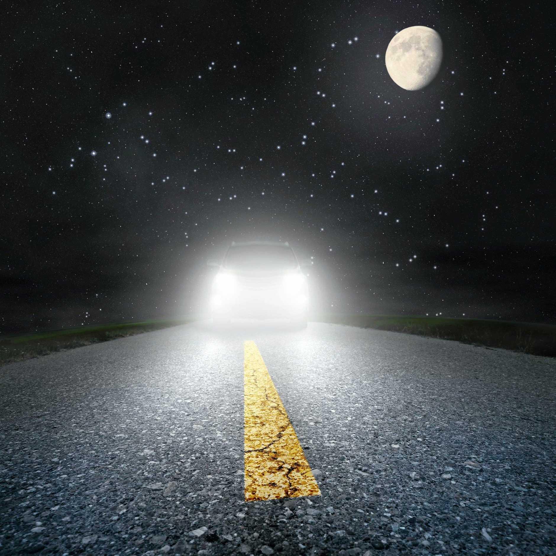Night driving on an asphalt road towards the headlights