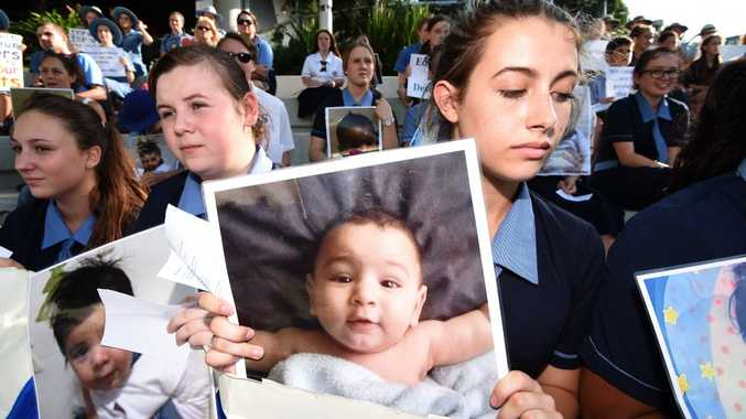 School students hold photos of a baby girl known as Asha during a protest outside the Lady Cilento Children's Hospital in Brisbane on February 18, 2016. The hospital had refused to release Asha, being treated for burns suffered while in detention on Nauru until a