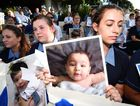 "School students hold photos of a baby girl known as Asha during a protest outside the Lady Cilento Children's Hospital in Brisbane on February 18, 2016. The hospital had refused to release Asha, being treated for burns suffered while in detention on Nauru until a ""suitable"" home is found. (AAP Image/Dan Peled)"