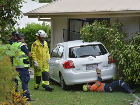 Firefighters investigate a car that crashed into a house at Buderim.