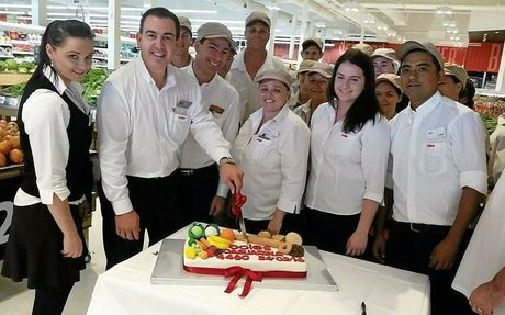 Steve Meli cuts a cake with some of his new employees at the new Casuarina Coles.