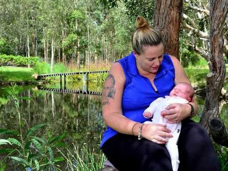 Jessica Watson holds her daughter Evelyn Lane next to the dam that claimed the life of her son, Conan six years ago.