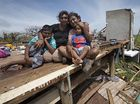 Sanjogeeta Kiran, right, with her sister Sulva Kiran, and her son Shivendera, 10, and 2 year-old Raajeen, in the wreckage of their home in RakiRaki, Fiji. Photo / Brett Phibbs.