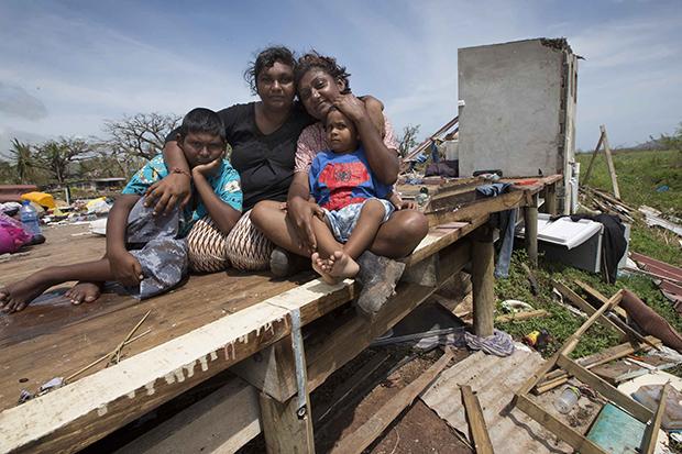 Sanjogeeta Kiran, right, with her sister Sulva Kiran, and her son Shivendera, 10, and 2 year-old Raajeen, in the wreckage of their home in RakiRaki, Fiji. Photo / Brett Phibbs.