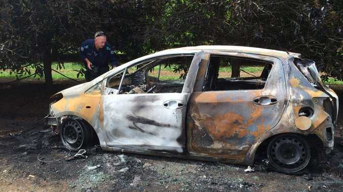 BURNT OUT: Police investigate after a car stolen from Kepnock overnight was dumped at Woongarra and torched. Photo Craig Warhurst/ NewsMail
