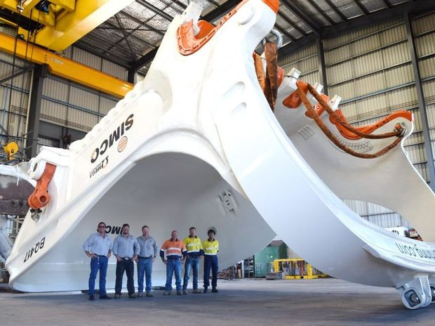 Dwarfed by the huge dragline bucket at the Independent Mining Services Qld workshop at Paget are (from left) IMS director Gary Brown, IMS business development manager Ryan McGovern, IMS operations manager Michael Hilton, SIMCO director Marty Simpson, SIMCO support manager Barry Manning and SIMCO mechanical engineer Sam Hasnat. Photo Alan Quinney / Daily Mercury