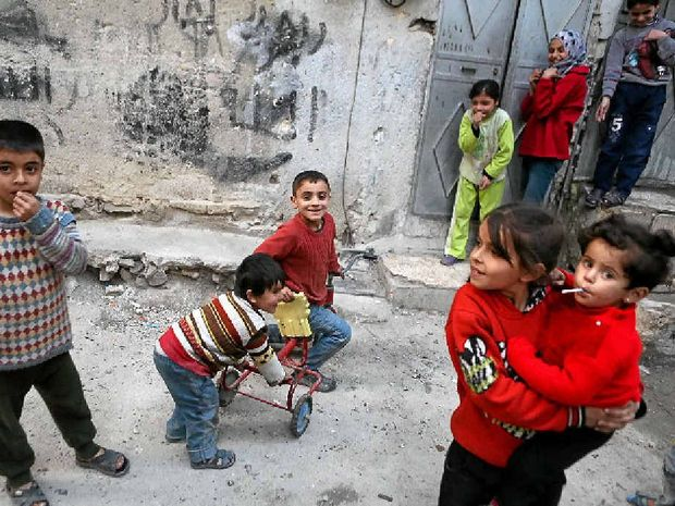 RELIEF: Syrian children play outside their home in a Damascus suburb after the ceasefire came into effect.