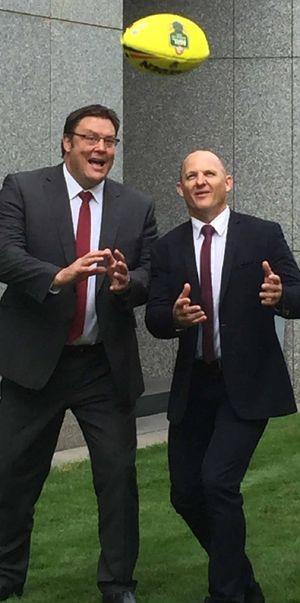 FLICK PASS: Senator Glenn Lazarus (left) with political aspirant and former teammate Kerrod Walters.