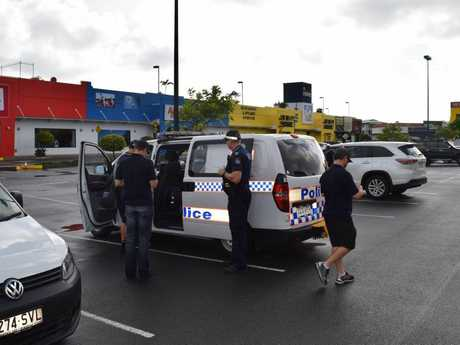 Crew members from television show The Force- Behind the Line and Maroochydore police officers leave the scene of a break-in at Maroochydore Cash Converters.