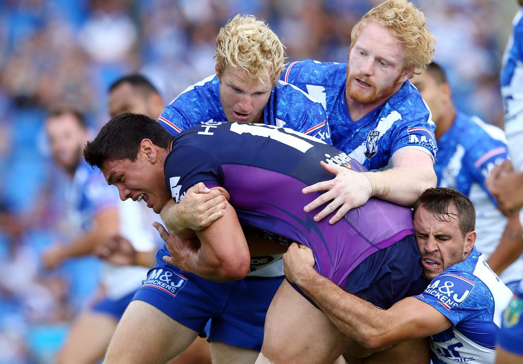 Jordan McLean, of the Storm, is tackled by Aiden Tolman, James Graham and Josh Reynolds, of the Bulldogs, during the NRL Trial match. Photo: Renee McKay/Getty Images.