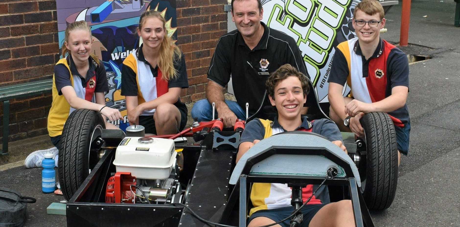 RACING TO LEARN: Warwick High students Evie Angell, Symantha Boyce, Nathan Walker, Austin Greenaway (seated) and teacher Michael Plant check out a Formula student made race car.