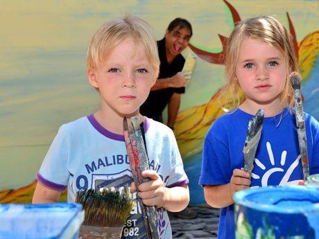 Johnathon Mason, 4 and Sari Smith, 3 help Aboriginal artist Arthur Conlon paint a mural at C&K Cotton Tree Community Child Care Centre.
