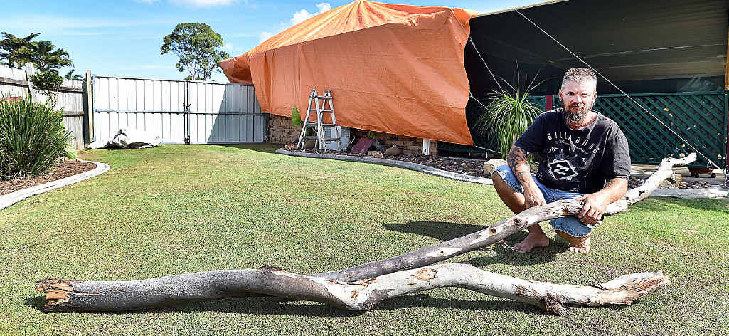 STORM DAMAGE: Eli Waters resident Troy Mitchell with the branch that speared through his patio sliding door from a gum tree in the park behind his house.