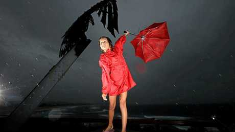 STORMY WEATHER: Tweed Heads local Amy Van Den Akker struggles to keep hold of her umbrella during short-lived heavy rain and wind on the Tweed Coast earlier in the week.