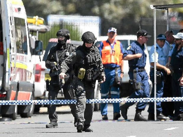 ON HIGH ALERT: Tactical police form a perimeter around a Sydney factory on Monday following the shooting death of a man and wounding of two other people.