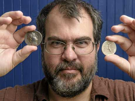 Matthew Shillam shows off two of his ancient coins as part of his