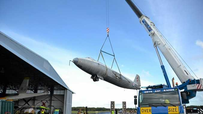 The Canberra Bomber is lifted by crane off the back of the truck that brought it to Evans Head from Amberley RAAF base.