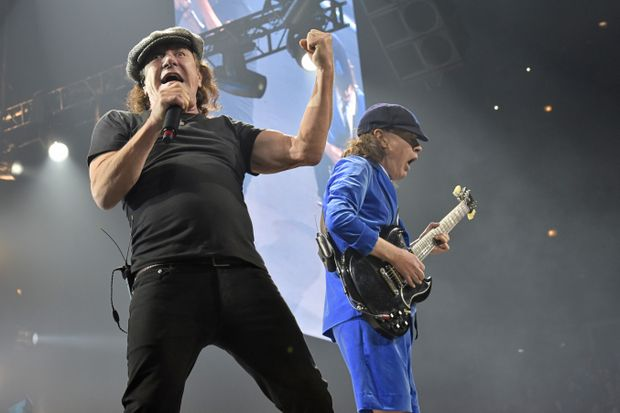 Brian Johnson, left, and Angus Young perform with AC/DC on the Rock or Bust Tour in Chicago last month. The band is postponing the remaining dates of their US tour because of Johnson's possible hearing loss. Photo: AAP