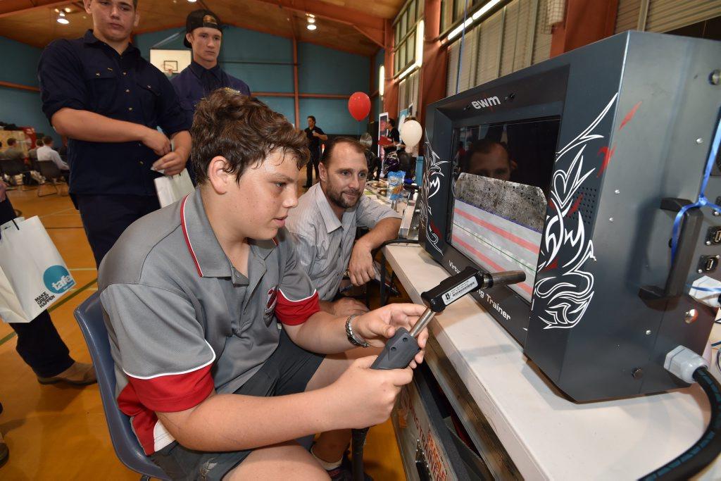 Tafe East Coast trades open day - yr10 student Zachary Staunton tests his skill on the Virtual Welding Trainer as BOC area mgr. Patrick Bortignon looks on. Photo: Alistair Brightman / Fraser Coast Chronicle