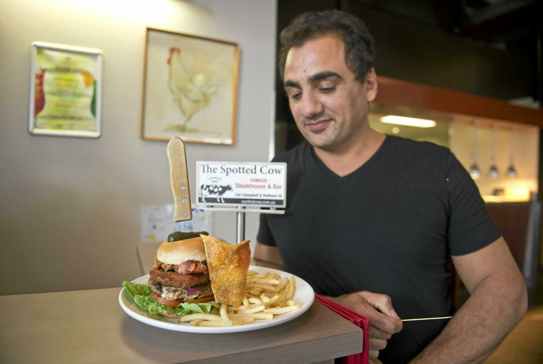 HUNGER CHALLENGE: Phil Coorey from the Spotted Cow contemplates biting into the new Triple Threat burger.