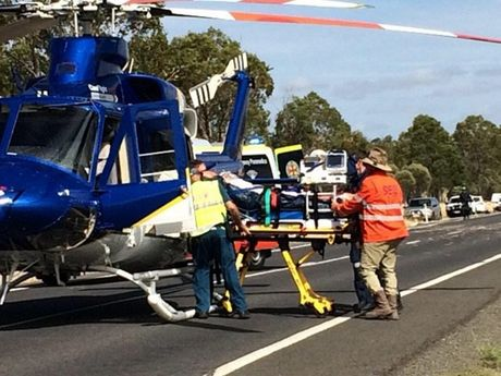 Patients are loaded into a rescue helicopter from the scene of a fatal crash on the Warrego Hwy.