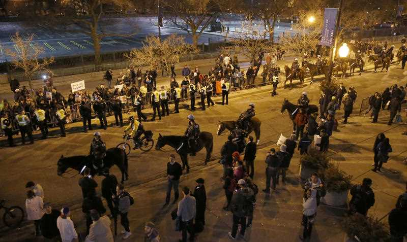 Chicago police officers on foot and mounted, watch over protesters after a rally for Republican presidential candidate Donald Trump was cancelled due to security concerns, on the campus of the University of Illinois-Chicago, Friday, March 11, 2016, in Chicago.