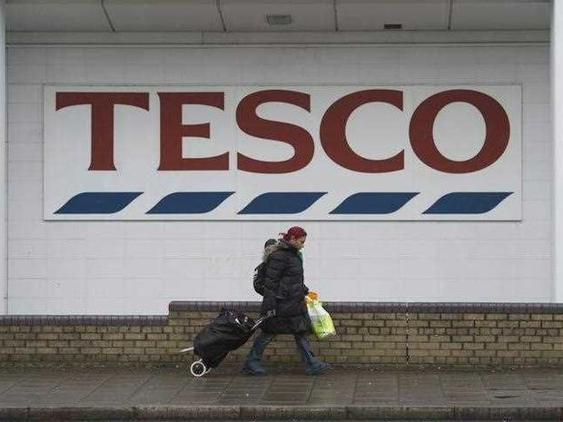 A woman walks past a Tesco supermarket store in London, Britain, 26 January 2016.