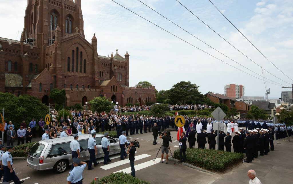 SOLEMN OCCASION : A large crowd farewells NSW police sergeant Geoffrey Richardson in Newcastle.
