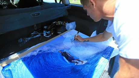 """Mick Fanning puts the finishing touch on one of Simon """"Swilly"""" Williams' photos of him in the surf. The print will be auctioned off to raise money for the Gold Coast World Surfing Reserve on Thursday."""