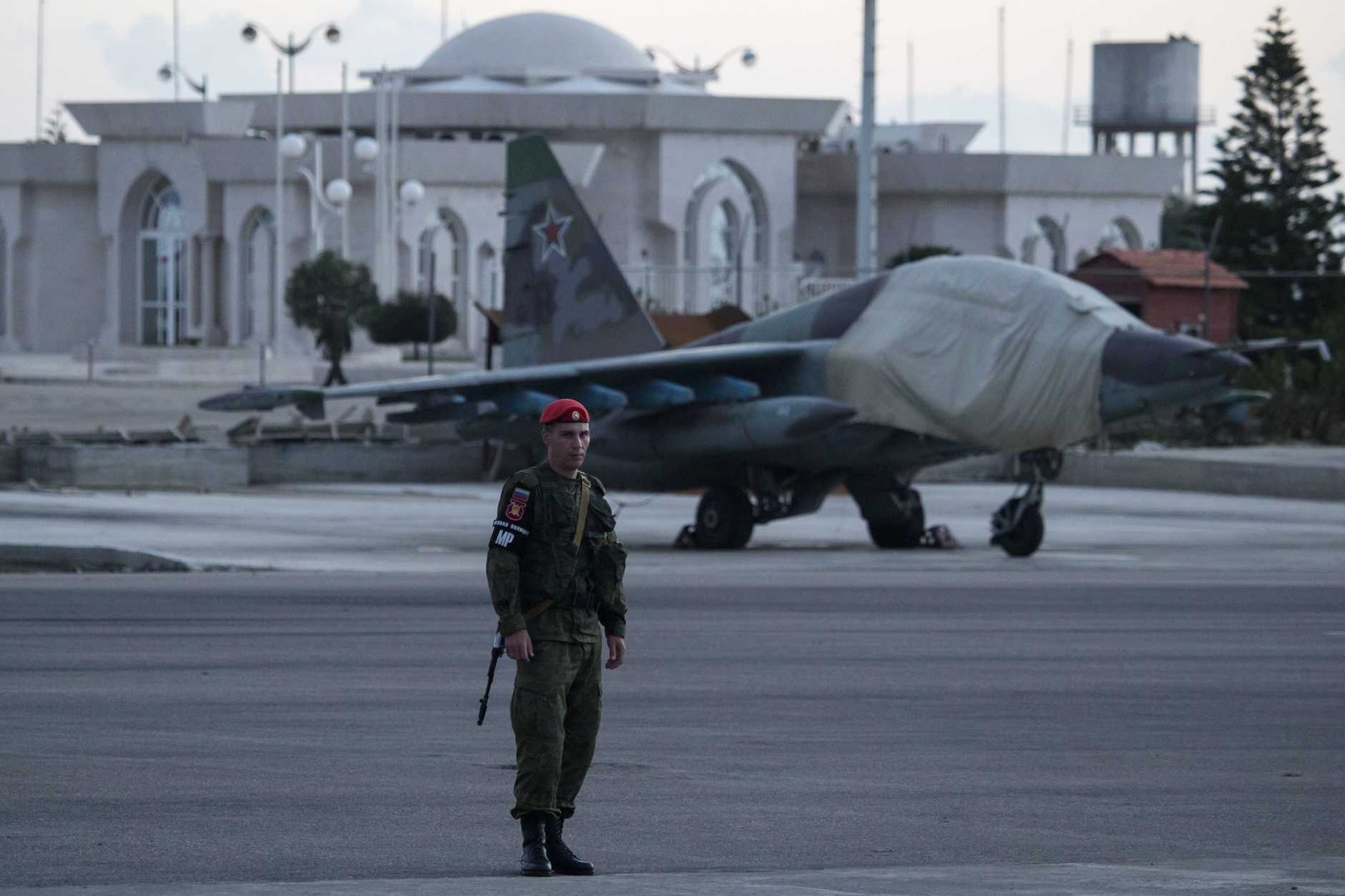 A Russian soldier guards a jet parked at Hemeimeem air base in Syria. Russian warplanes have mostly stayed on the ground since the cease-fire began. Photo: AP