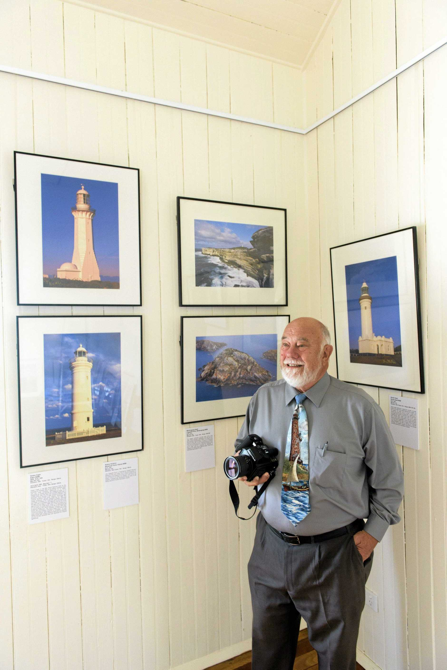 Photographer John Ibbotson with his exhibition of lighthouse photos at the Old Kirk at the Yamba Museum raising money for the Light Up the Darkness program.