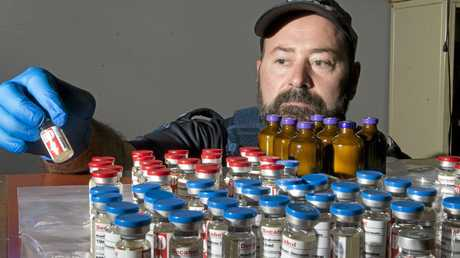 STEROID STASH:  Tactical Crime Squad Constable Scott Nolan inspects the seized drugs  . Wednesday 16 Mar , 2016.
