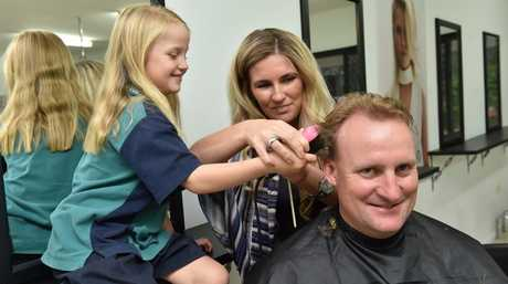 Olivia Heckels helps hairdresser Natalie Hoult shave her dad Ash's head to raise awareness and funds for Leukaemia. Photo: Alistair Brightman / Fraser Coast Chronicle
