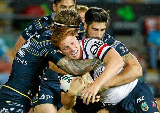 CAUGHT: The Roosters' Dylan Napa tackled by Cowboys' Ethan Lowe and James Tamou.