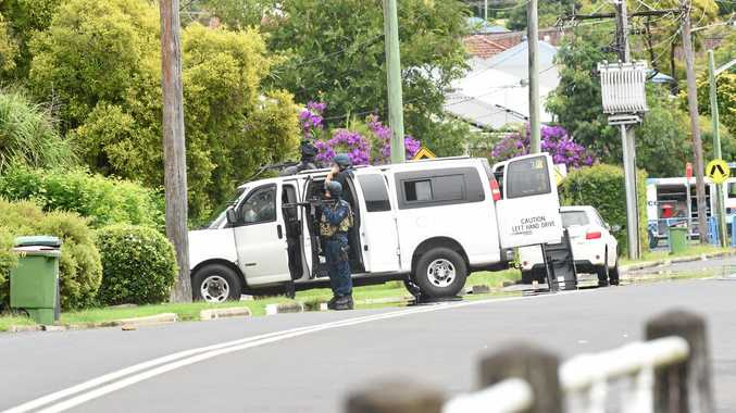 NO EASY JOB: A police negotiator surrounded by officers from the State Protection Support Unit at the scene of the siege in Dalley St, East Lismore.