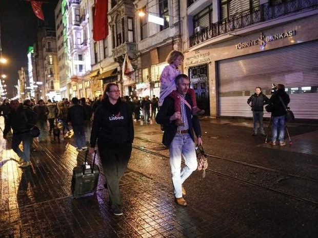 Tourists walk on the street near the scene of a bomb explosion in the downtown Istiklal Street earlier the same day, in Istanbul, Turkey, 19 March 2016. The suicide bomb explosion according to media reports caused the lives of at least five people whil 36 others - among them a dozen foreigners - were injured in the blast, some of them seriously.