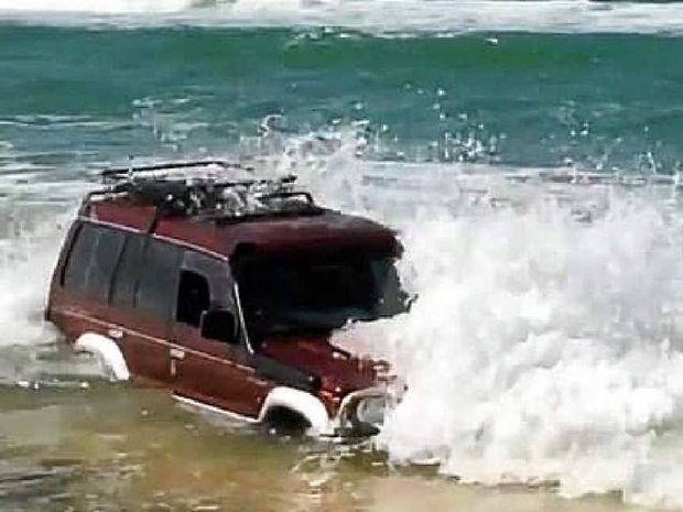 RUINED: A 4WD is swamped after becoming stuck on the Mudlo Rocks at Double Island Point on Friday.