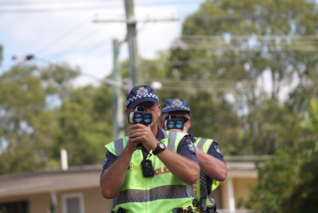 Queensland Road Policing Unit Senior Constable Paul Taylor (front) and Senior Constable Davin Cole check the speeds of people driving in a 70kmh zone.