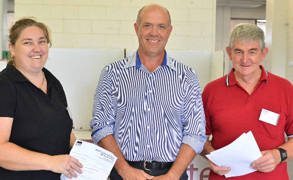 MAN IN THE MIDDLE: Electoral assistant Kelly Garner (left) and returning officer Ken Garner (right) congratulate the official election winner for Division 3, Mal Gear, after Mr Garner declared the official poll result yesterday.