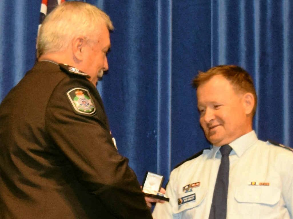 Sunshine Coast district duty officer Senior Sergeant Michael Buckley receives a 35-year clasp to his Queensland Police Service Medal from Assistant Commissioner Alistair Dawson.