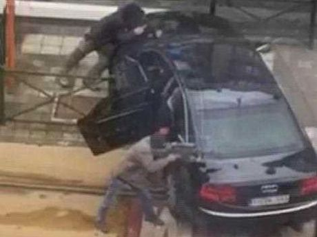 In this frame made from video, armed officers point their weapons in the direction of an injured man, in Brussels, Belgium, Friday March 25, 2016. Police again raided a number of Brussels neighbourhoods on Friday in an operation a local official said was linked to both the airport and metro bombings and to the arrest in the Paris suburbs of a man who may have been plotting a new attack in France.