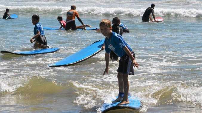 HANG TEN: Gillwinga students get into some surfing action at Woolgoolga main beach.
