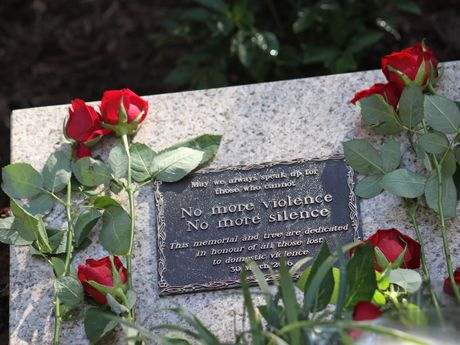 Red roses surround the plaque dedicated to Queenslanders lost to domestic violence.