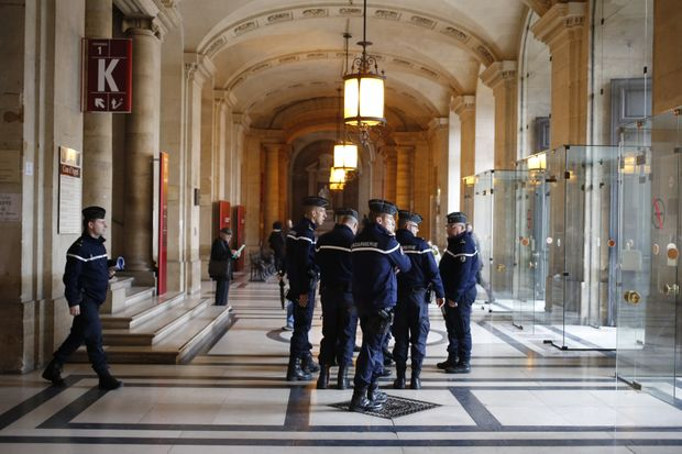 French gendarmes patrol in the Paris hall of Justice while Reda Kriket is being questioned by a magistrate who then filed preliminary terror charges.