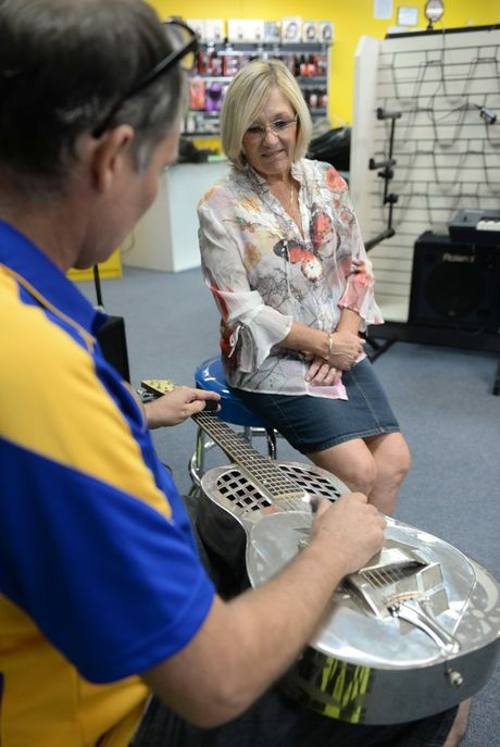 MEMORIES: Gavin Hunter plays for Robyn Cox with her father's 78-year-old guitar, now restored. Photo: Max Fleet / NewsMail