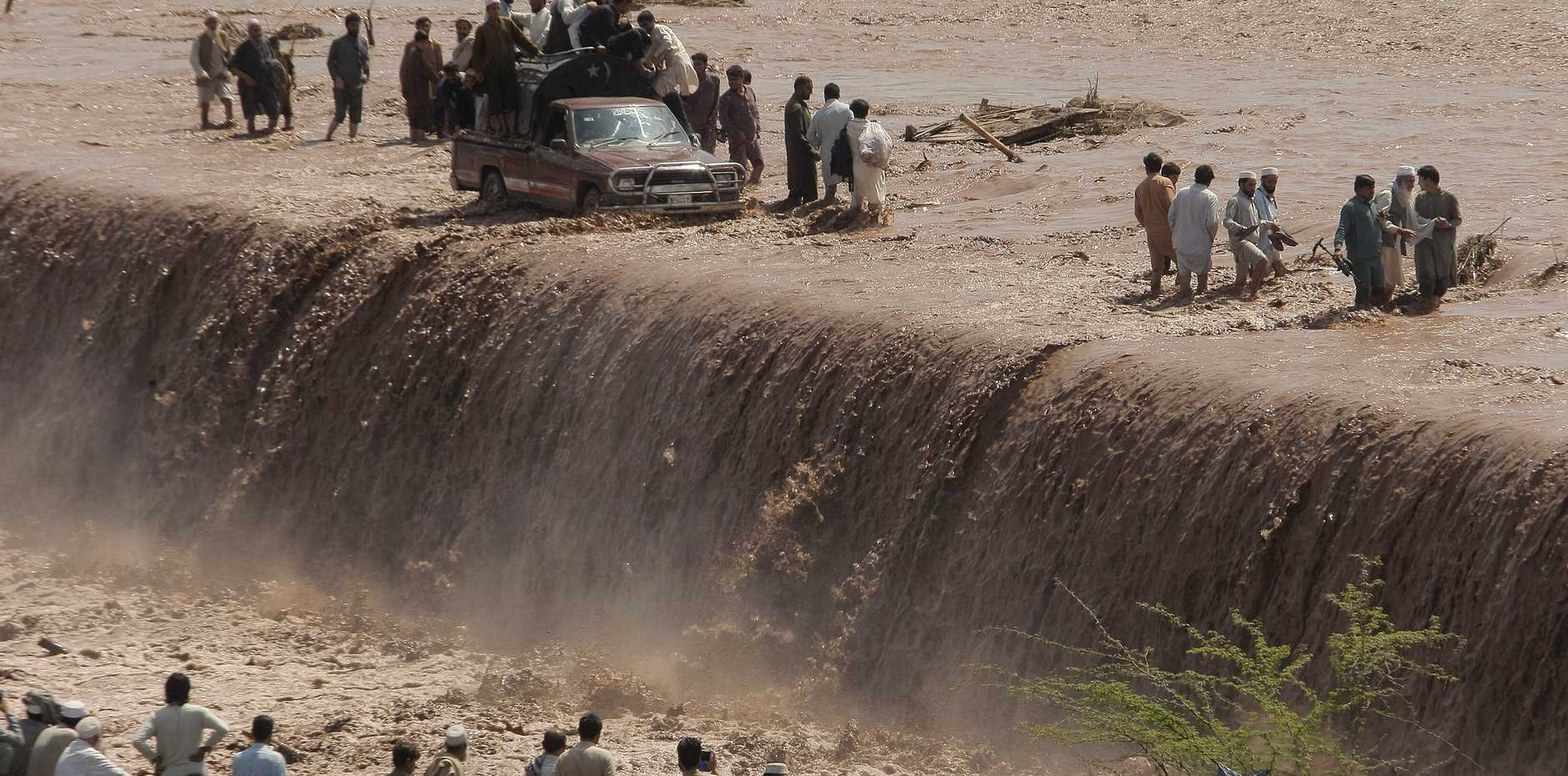 Pakistani villagers wade across a flooded road after heavy rain on the outskirts of Peshawar, Pakistan. Flash floods triggered by torrential rains Sunday killed dozens of people in northwest Pakistan, officials said.