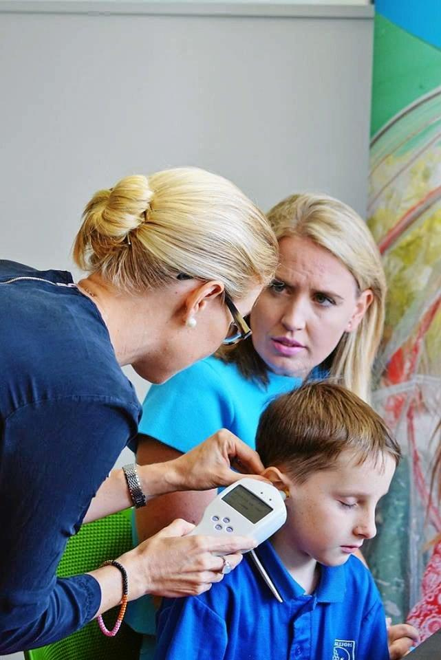 LISTEN UP: Minister for Health Kate Jones watches on as young Lewis Mather has his hearing tested at the event launch.