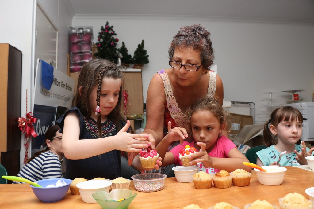 Workshop organiser Lucy Dillon is helping Allanah Counsell and Charlie Benson decorate their cupcakes.